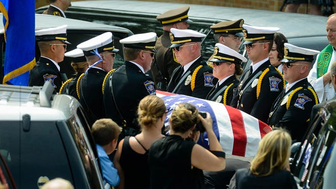 Pall bearers lift the casket of Mendota Heights police officer Scott Patrick into a hearse following funeral services at St. Stephen's Lutheran Church in West St. Paul, Minn.