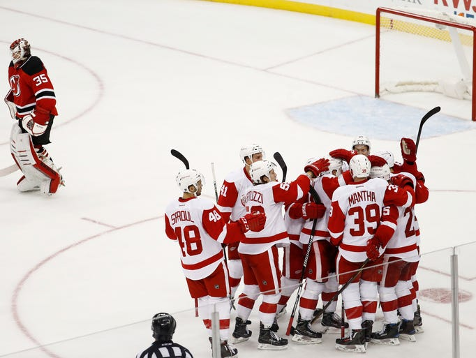 Detroit Red Wings players celebrate Mike Green's game-winning