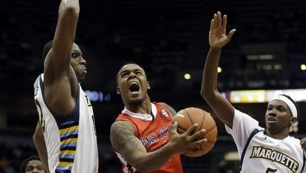 Ball State's Zavier Turner tries to drive between Marquette's John Dawson and JaJuan Johnson (5) during the second half of an NCAA college basketball game Tuesday, Dec. 17, 2013, in Milwaukee. (