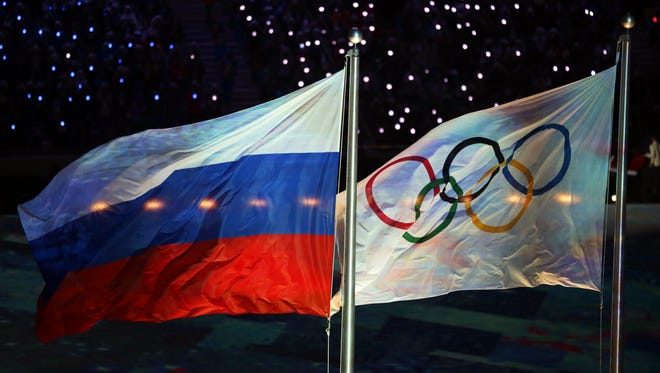 A file photo dated February 2014 of the Olympic flag (right) and the Russian flag (left) during the closing ceremony of the Sochi Olympic Games.
