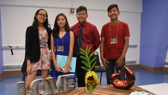 """From left, Naomi Aldan, Kaye Gallardo, Jesus Toves and Kenneth Quilit show off their entry in the Sustainable Technologies and Environmental Education Program silent auction at Guam Community College on Thursday, June 21, 2018. Students held the silent auction for the coffee tables and benches that they created using recycled pallets, and for the floral arrangements they designed using local flora and fauna, housed in various recycled containers. The team pictured won the """"people's choice of best-built set"""" award."""
