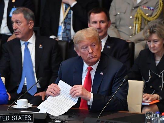 US President Donald Trump gestures after arriving for