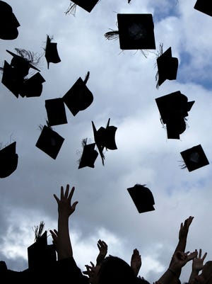 Graduates toss their caps.