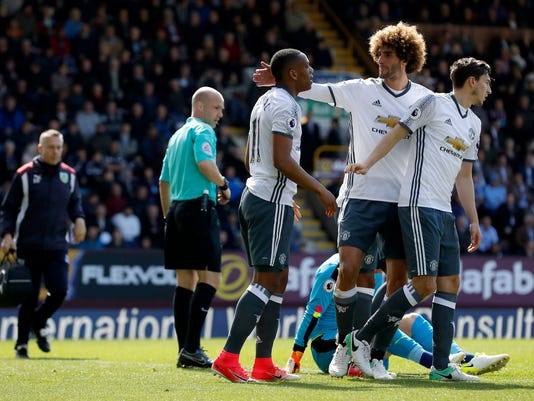 Manchester United's Anthony Martial, left, celebrates scoring his side's first goal of the game against Burnely, during their English Premier League soccer match at Turf Moor in Burnley, England, Sunday April 23, 2017. (Martin Rickett/PA via AP)