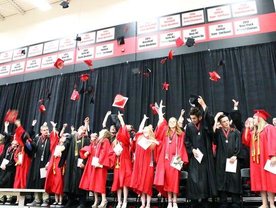 High school graduates throw their caps to celebrate.