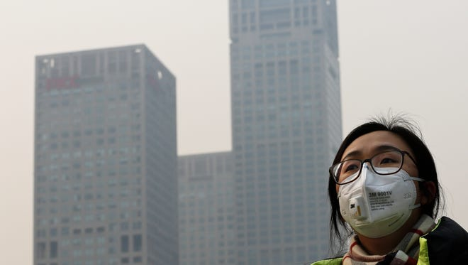 A woman wearing a face mask to protect herself from pollutants walks past office buildings shrouded with pollution haze in Beijing, Monday, Dec. 7, 2015. Beijing issued its first-ever red alert for smog on Monday, urging schools to close and invoking restrictions on factories and traffic that will keep half of the city's vehicles off the roads.
