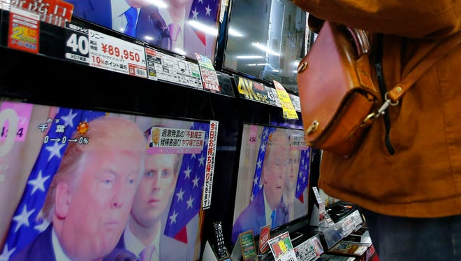 A shopper looks at flat-panel TVs showing Republican's front-runner candidate Donald Trump in a news program on the U.S. presidential election's Super Tuesday at an electronics store in Tokyo, Wednesday, March 2, 2016. After the Super Tuesday primaries and caucuses in a dozen states, Trump and Democrat candidate Hillary Clinton had tightened their grasp on their party's presidential nominations.