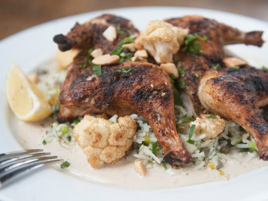 Whole poussin is grilled and served in tahini sauce with cauliflower and jeweled Iranian rice at Kanella in Philadelphia.