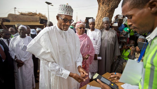 Opposition candidate Gen. Muhammadu Buhari, center, arrives to validate his voting card using a fingerprint reader, prior to casting his vote later in the day, in his home town of Daura, Nigeria Saturday, March 28, 2015. Nigerians went to the polls Saturday in presidential elections which analysts say will be the most tightly contested in the history of Africa's richest nation and its largest democracy.