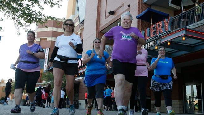 Bob Platt of Oakley (center, in purple) prepares to run with his training group. The Flying Pig will be his 150th marathon.