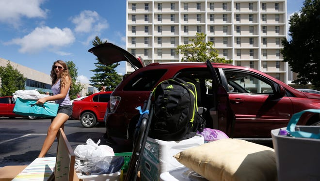 Freshman Jillian Hays unloads her belongings out of the car outside of Freudenberger House during move-in-day on the MSU campus on Friday, August 19, 2016.