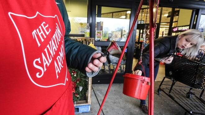 Elizabeth Gatten, right, puts a donation in the Salvation Army donation kettle in front of Kroger's in the Highlands.  The bell ringer was Timothy Smith.November 28, 2016