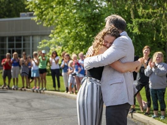 Fred and Greta Warmbier embrace as the family stops