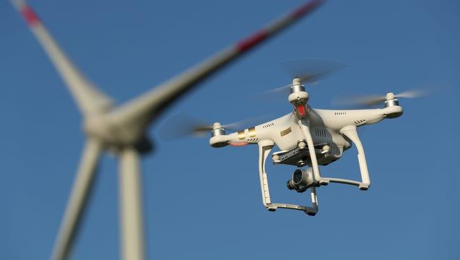 A DJI Phantom multirotor drone flies near a wind farm on June 8, 2016 near Brueck, Germany.
