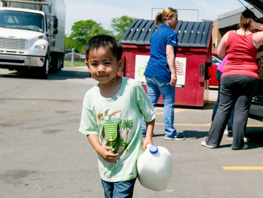Jayden Hang, 5, of Warren carries milk to his car at