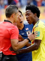 Carlos Sanchez (R) of Colombia reacts after being sent
