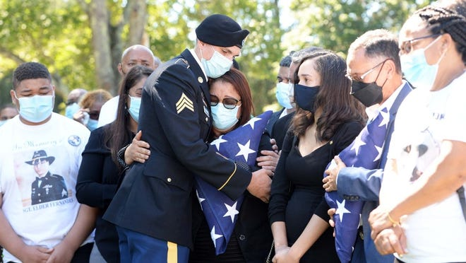 Ailina Neves Fernandes, the mother of Sgt. Elder Fernandes, receives a hug from an U.S. Army Sergent William Channell, as  family watches on at Melrose Cemetery on Saturday September 5, 2020.