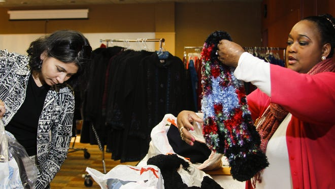 Women's Center of Greater Lansing board member Reshma Sambare left, and Lansing Community College intern Londa Owens, of Lansing, sort donated clothing at a Holiday Fashion Boutique clothing drive on Dec. 6, 2015 at the Kellogg Hotel & Conference Center in East Lansing. The clothing was donated to the Women's Center for its Professional Clothing Closet