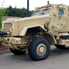 A Mine-Resistant Ambush Protected (MRAP) vehicle sits in front of police headquarters in Watertown, Conn.