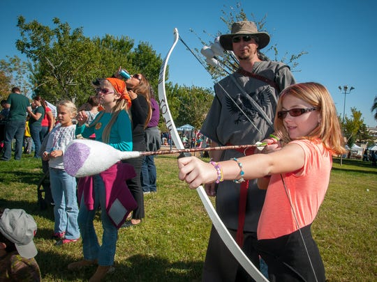 Kadence Johnson, 8, works on her bow and arrow skills under the tutelage of Keith Knodle during the 44th annual Renaissance ArtsFaire at Young Park on Saturday.