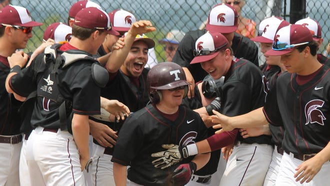 Turpin manager Daniel Jones is mobbed by his teammates after scoring a run.