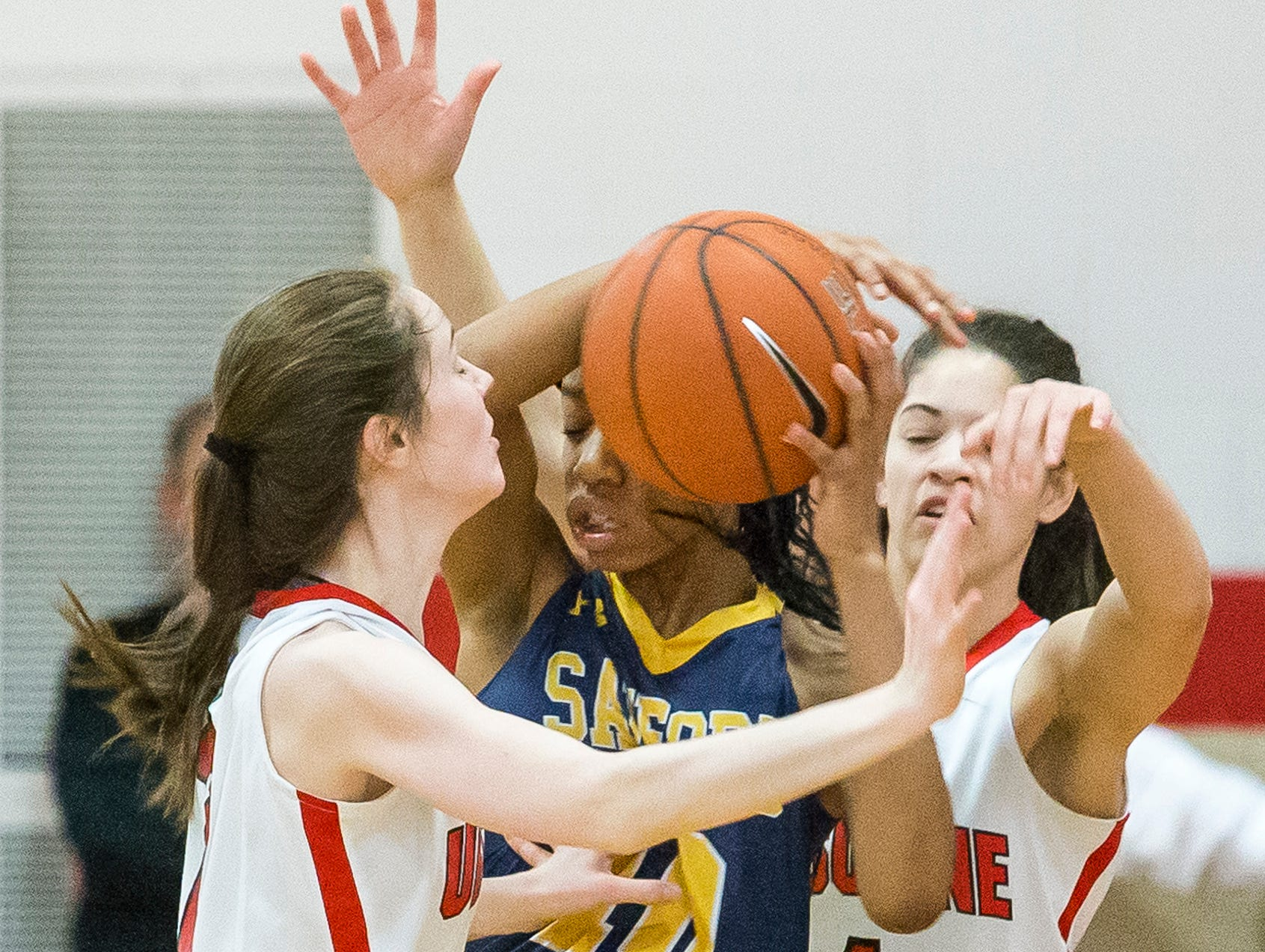 Ursuline's Maggie Connolly (left) and Alisha Lewis (right) trap Sanford's Kanisha Tucker in the second half of Ursuline's 50-40 win over Sanford at Ursuline Academy on Thursday night.