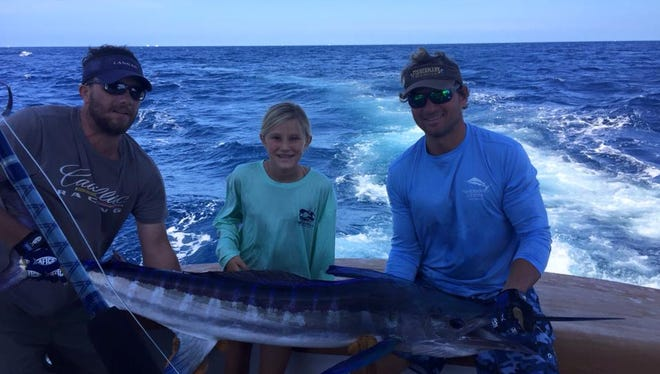 Alexis Nowakowski (center) caught a white marlin near the Baltimore Canyon on a naked ballyhoo. Also pictured are Captain Freddy Wick and Kenny Simpler.