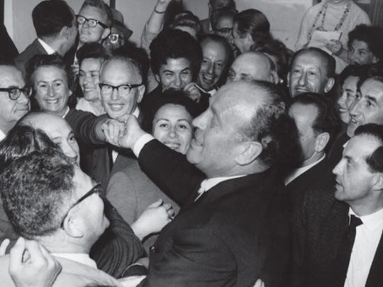 Oskar Schindler greets a crowd at the Jerusalem airport