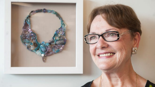 Janet Knowles of Moorestown, a breast cancer survivor and philanthropist who donated $5 million and personally committed to advance Cooper's breast cancer program seven years ago, stands beside her work A New Beginning' that hangs in the breast cancer center that bears her name.