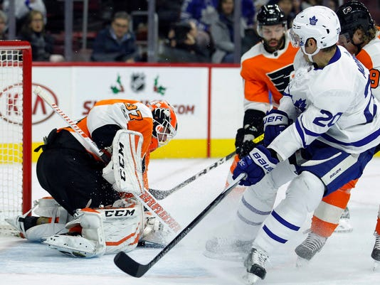 Philadelphia Flyers' Brian Elliott, left, covers up the shot attempt by Toronto Maple Leafs' Dominic Moore, right, during the first period of an NHL hockey game, Tuesday, Dec. 12, 20017, in Philadelphia. (AP Photo/Tom Mihalek)