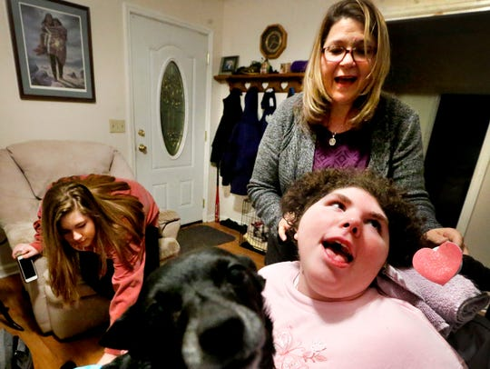 """Alison """"Ally"""" Roan was born with Spastic Quadriplegic Cerebral Palsy. She reacts as family dog Bella climbs into her lap as mother Rosemarie Roan while in the living room of their home. Anna Roan is in the background."""