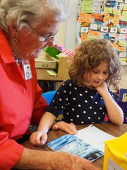 """""""Grandma"""" Lucille Wuest reads a book about dolphins"""