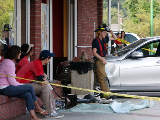 Employees watch as New York State police and Goldens Bridge firefighters work to clear a car that crashed into the Dunkin Donuts / Baskin Robbins in the Goldens Bridge shopping center at Routes 138 and 22 in Goldens Bridge Aug. 6, 2010. (Frank Becerra Jr./ The Journal News)