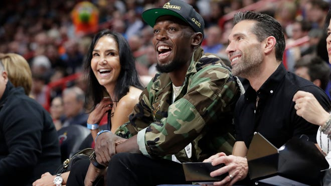 In this Dec. 13, 2019 file photo, Usain Bolt watches the first half of an NBA basketball game between the Miami Heat and Los Angeles Lakers in Miami. Jamaica's Minister of Health Christopher Tufton said on Monday, Aug. 24, 2020 that the legendary sprinter has tested positive for the novel coronavirus.