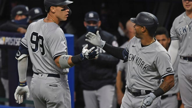 New York Yankees' Aaron Judge (99) is congratulated by Aaron Hicks after hitting a two-run home run off Cleveland Indians starting pitcher Shane Bieber (57) in the first inning of Game 1 of an American League wild-card baseball series, Tuesday, Sept. 29, 2020, in Cleveland.