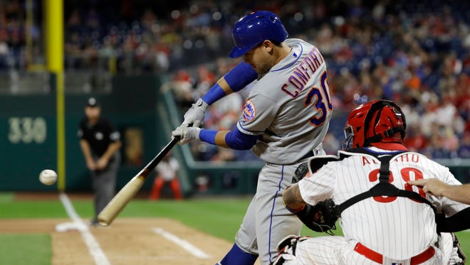 New York Mets' Michael Conforto, left, hits a two-run home run off Philadelphia Phillies relief pitcher Hector Neris during the ninth inning of a baseball game Friday, May 11, 2018, in Philadelphia. At right is catcher Jorge Alfaro. New York won 3-1.
