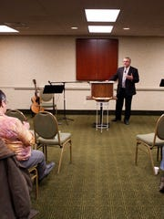 The Rev. Tom Rouse leads a service at the La Quinta Inn Oak Room in Grand Chute on Sunday.