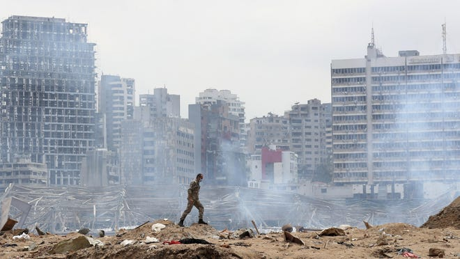 A soldier walks at the devastated site of the explosion in the port of Beirut, Lebanon, Thursday Aug.6, 2020. French President Emmanuel Macron came in Beirut to offer French support to Lebanon after the deadly port blast.
