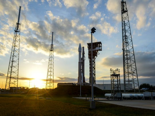 An Atlas V rocket sits on the pad at Launch Complex 41 as the sun goes down