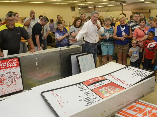 Rapides Parish Police Juror Bubba Moreau (center, white shirt) points to items about to be auctioned at the Rapides Parish Coliseum auction held Saturday.