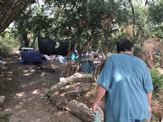 Scott Heiser visits a campsite along the Concho River in San Angelo on Tuesday, June 12, 2018, where his homeless friend  Billy is recovering from an injury.