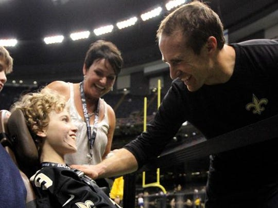 New Orleans Saints quarterback Drew Brees (9) talks to J. D. Blue before their game against the Baltimore Ravens at Mercedes-Benz Superdome.