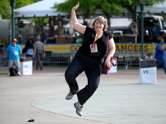 Executive director Missy Paschke-Wood leaps into the air in excitement while preparing for the opening ceremonies of Festival International de Louisiane in Lafayette. As the director, Paschke-Wood has announced the introduction of paid passes to the free festival that would give guests access to bathrooms, express beverage lines and a rooftop lounge overlooking Parc Sans Souci.