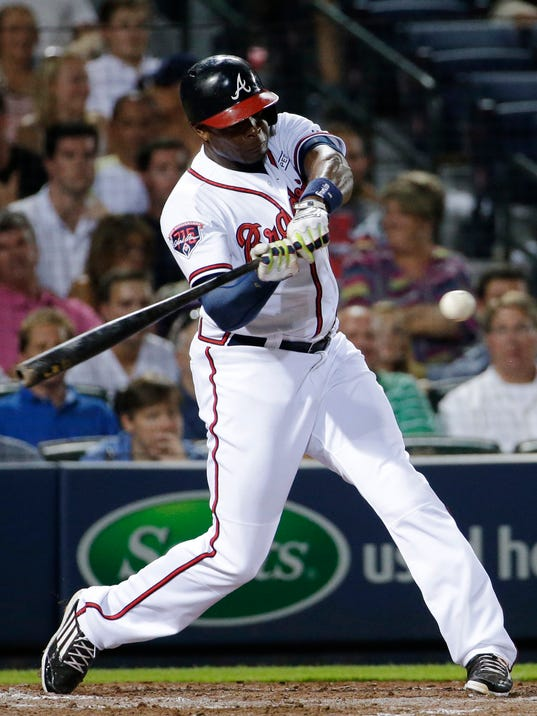 Atlanta Braves' Justin Upton swings to hit a single to score teammates Jason Heyward and Emilio Bonifacio in the seventh inning of a baseball game against the Miami Marlins, Friday, Aug. 29, 2014, in Atlanta. (AP Photo/David Goldman)