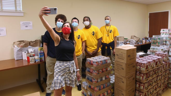 """New Jersey First Lady Tammy Murphy takes a """"selfie"""" with students in the New Jersey Youth Corps Program. From left, Xavier Gonzalez, 18, of Long Branch, Max Westling, 16, of Vernon, Chris Perez, 17, of Franklin and Jayden Melendez, 17, of Vernon inside Project Self-Sufficiency's food pantry on Thursday."""