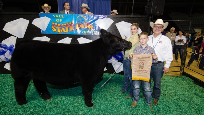 """Mountain Home's Mackenzie Morrison and her grand champion market steer """"Boa Boa"""" are pictured with Stran Wagner, (holding banner) of Berryville, and Randy Veach, of Manila, president of Arkansas Farm Bureau."""