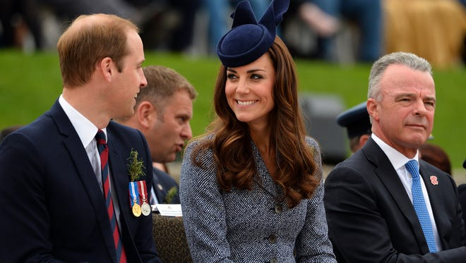 Britains Prince William (L) and his wife Catherine, Duchess of Cambridge, share a smile during the ANZAC Day march at the Australian War Memorial in Canberra on April 25, 2014.