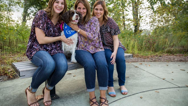 Kendall, Holly and Heidi Bryant sit with their dog Riley at Minnetrista Sept. 15. According to the Bryants, Riley has beena  source of comfort after Bill Bryant, Holly's husband and father of Heidi and Kendall, died from cancer in 2015.
