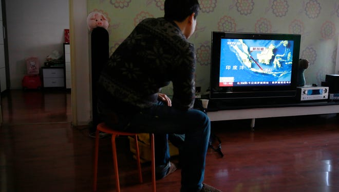 Jiang Hui, a relative of passengers on  Malaysia Airlines Flight 370, which went missing March 8, 2014, watches a TV news broadcast about missing AirAsia Flight 8501 at his house in Beijing on Dec. 28.