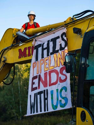 Rising Tide Vermont protestor Molly Stuart sits locked to the top of an excavator at a Vermont Gas pipeline construction site along Route 289 in Essex on Thursday, September 17, 2015.